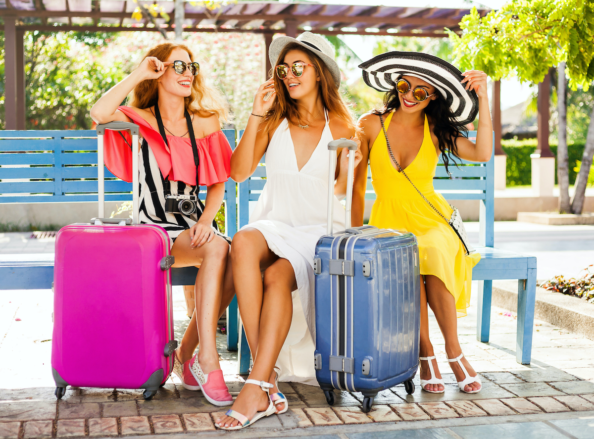 Three bridesmaids with bright colored luggage on bachelorette trip